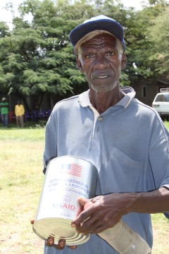 A food aid beneficiary after receiving a can of vegetable oil አንድ ተረጂ የምግብ ዘይት እርዳታ ተቀብለው