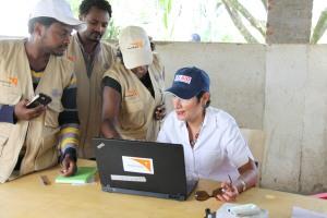 Aid workers explain to Ambassador Haslach how a food distribution system they use at the JEOP Food Distribution Center works የእርዳታ ሠራተኞች በምግብ ማከፋፈያ ማዕከሉ የሚጠቀሙበት የምግብ ስርጭት ሥርዓት እንዴት እንደሚሠራ ለአምባሳደር ሃስላክ ገለጻ ባደረጉበት ወቅት
