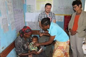 Ambassador Haslach observing a malnourished child being examined by a health extension worker at the health post አምባሳደር ሃስላክ በጤና ኬላው የጤና ኤክስተንሽን ባልደረባዋ በምግብ እጥረት ለተጎዳ ህጻን ምርመራ ስታደርግ ተገኝተው በተመለከቱበት ወቅት