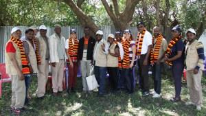 Ambassador Haslach posing for a group photo with emergency food aid workers at Abela Faricho JEOP Food Distribution Center አምባሳደር ሃስላክ በአቤላ ፋሪቾ ወረዳ በሚገኘው የምግብ እርዳታ ማከፋፈያ ጣቢያ ከእርዳታ ሠራተኞቹ ጋር በቡድን ፎቶ ሲነሱ