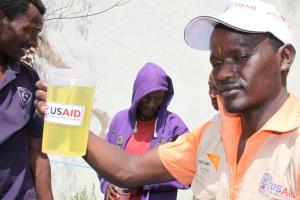 World Vision staffer distributing vegetable oil to food aid recipients at Abela Faricho JOEP Food Distribution Point, Humbo district በአቤላ ፋርቾ ወረዳ የወርልድ ቪዥን ባልደረባ ለእርዳታ ተቀባዮች የምግብ ዘይት ሲያድል