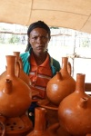 "An artisan from the Durame town displays coffee pots made with her ""Golden Hands."" Historically, this community of people has been discriminated against and denied access to education. They had limited economic opportunities aside from selling pottery within their communities. Today, with assistance from USAID, through KMG, things are slowly changing."
