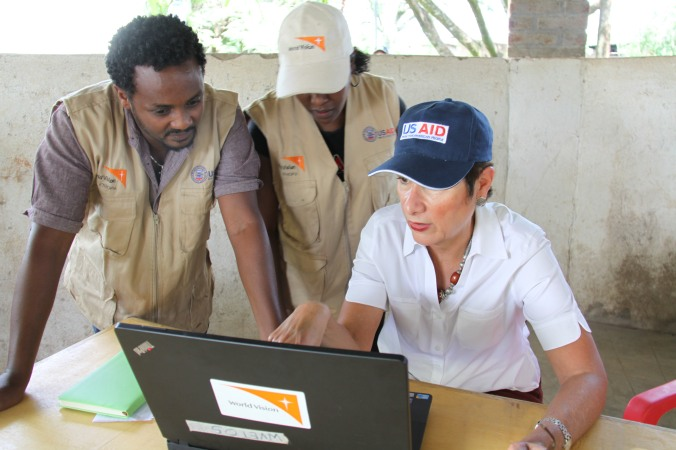 Ambassador Patricia M. Haslach is briefed on the food distribution and monitoring system by World Vision staff at one of the USAID-supported  food distribution sites in Arba Minch, SNNP. August 2015
